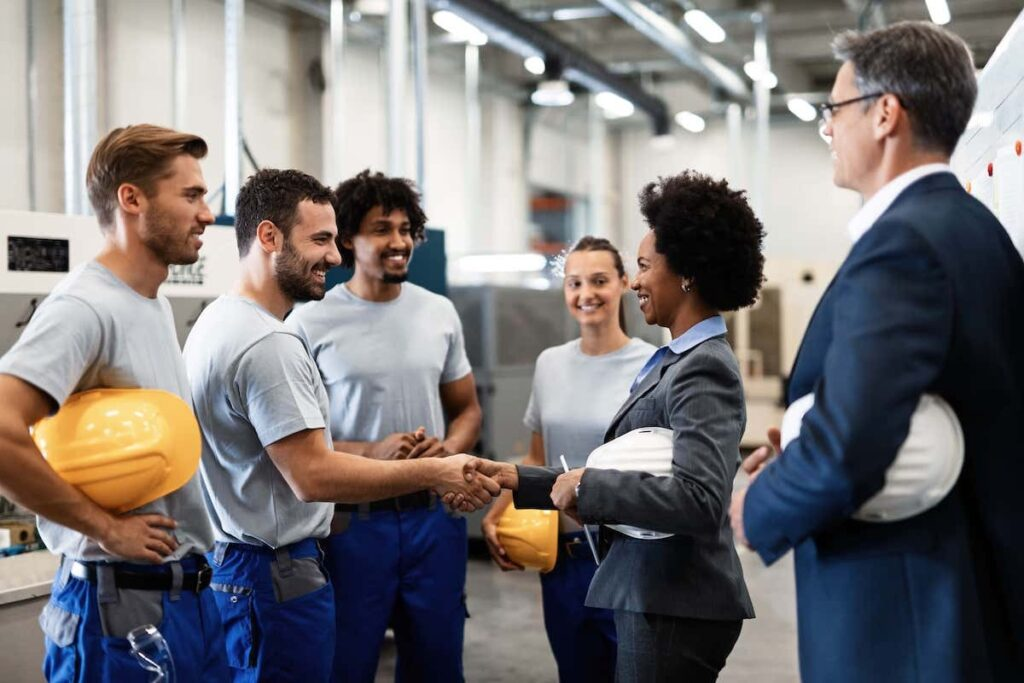 group of people at the factory greeting employees
